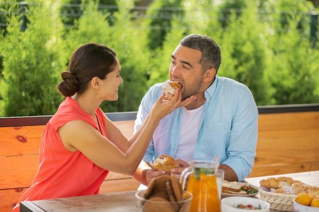 Croissant für ehemann. fürsorgliche und liebevolle frau, die lächelt, während sie ihrem mann ein croissant gibt