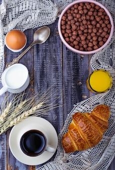 Croissant, getreideflocken, kaffee, milch, orangensaft, gekochtes ei zum frühstück