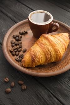 Croissant in der braunen platte und schwarzer kaffee in der tasse auf schwarzem holzhintergrund. standort vertikal.