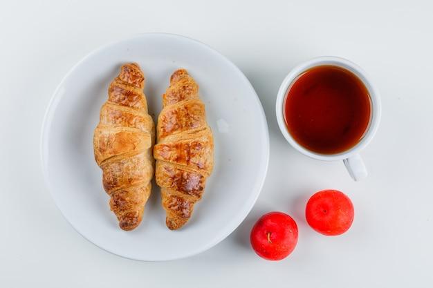Croissant in einem teller mit pflaumen, tee flach lag