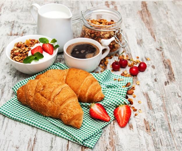 Croissant, kaffee, müsli und erdbeere
