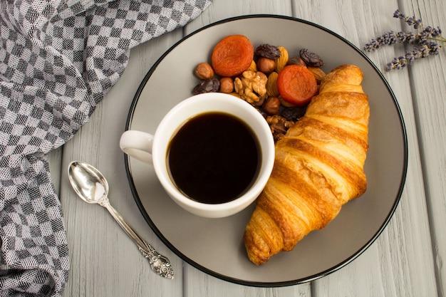 Croissant, kaffee, nüsse und getrocknete aprikosen auf dem grauen teller. blick von oben.