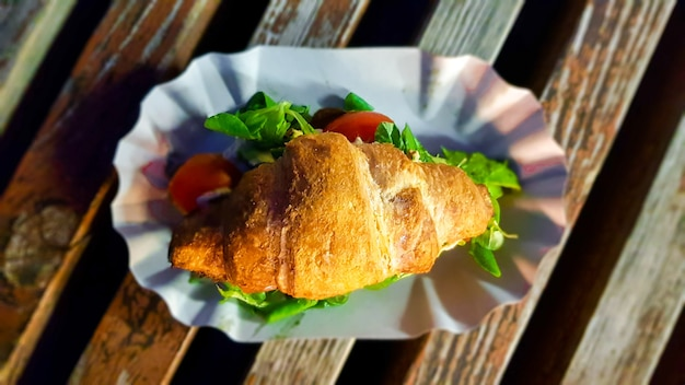 Croissant mit avocado, tomate und kräutern im freien. vegetarisches essen auf der straße.