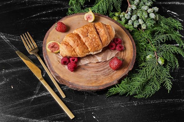 Croissant mit beeren auf holzplatte.