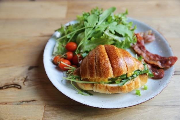 Croissant mit ei und speck auf holzhintergrund