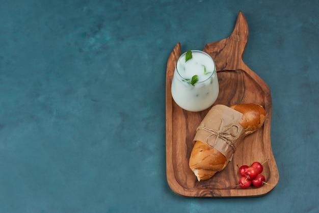 Croissant mit einer tasse milch und kirschen.