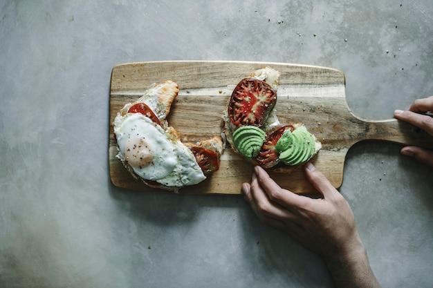 Croissant mit erbstück tomate, avocado und ein spiegelei