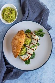 Croissant mit gegrilltem halloumi-käse, rucola und gegrillter zucchini. gesundes frühstück oder mittagessen.