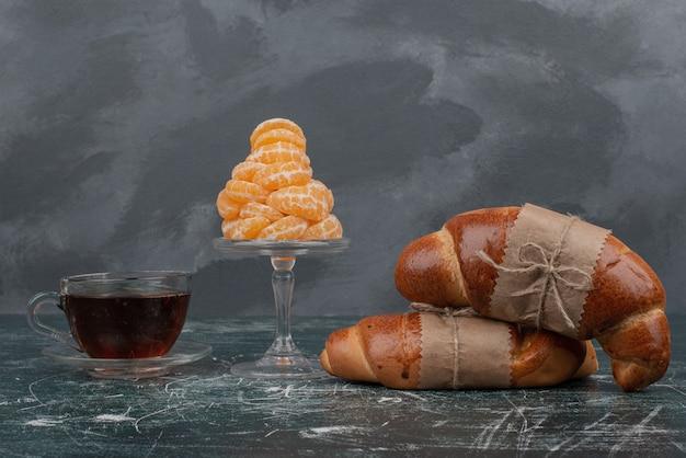 Croissant mit heißem tee und glasplatte mandarine