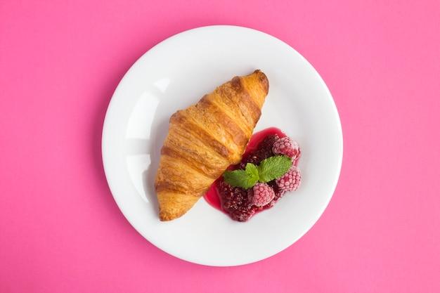 Croissant mit himbeermarmelade in der weißen platte in der mitte des rosa hintergrundes. ansicht von oben. platz kopieren.