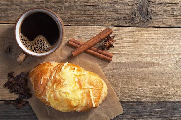 Croissant mit käse und heißem kaffee zum frühstück auf altem holzhintergrund, draufsicht. platz für text