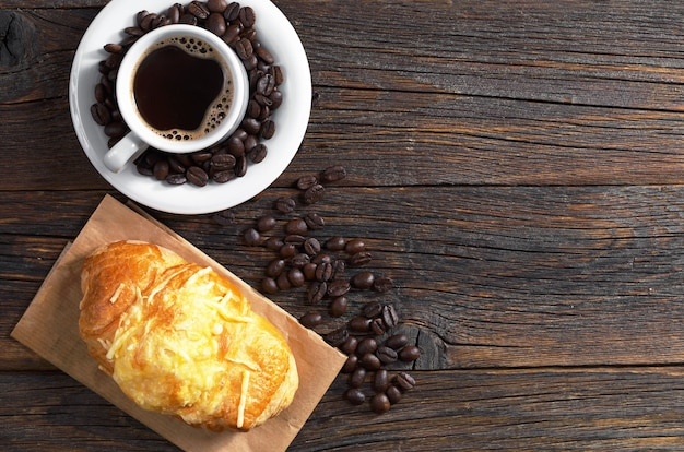 Croissant mit käse und heißem kaffee zum frühstück auf altem holztisch, draufsicht. platz für text