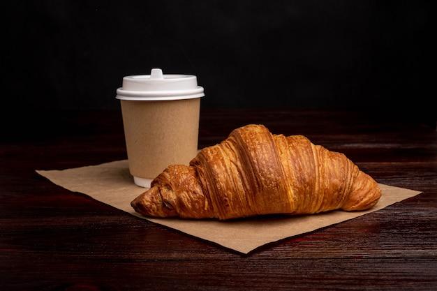 Croissant mit kaffee in eine pappbecher, frühstück zum mitnehmen