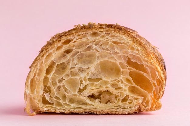 Croissant mit mandeln auf rosa hintergrund
