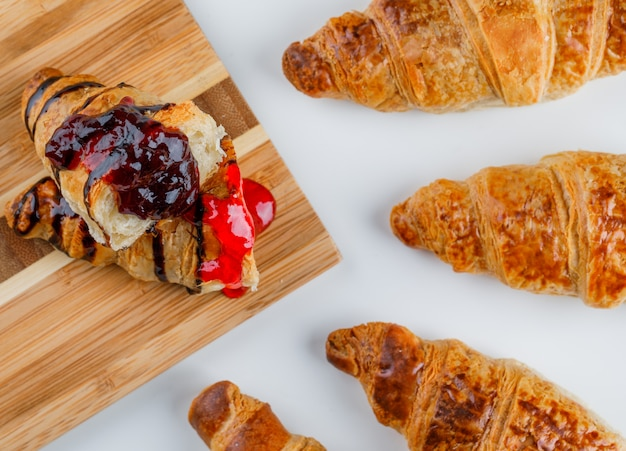Croissant mit marmelade auf weiß und schneidebrett, flach gelegt.