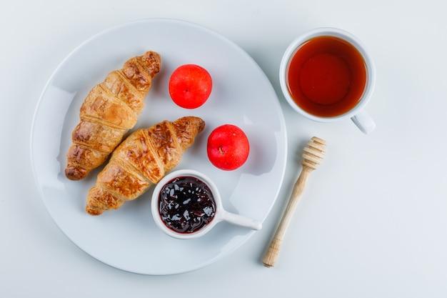 Croissant mit marmelade, pflaumen, schöpflöffel, tee auf einem teller, flach liegen.