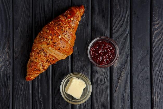 Croissant mit marmelade und butter. ansicht von oben.