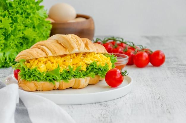 Croissant mit rührei, salat und kirschtomaten auf einem weißen teller mit zutaten zum kochen auf einem hölzernen hintergrund. horizontaler kopierbereich.