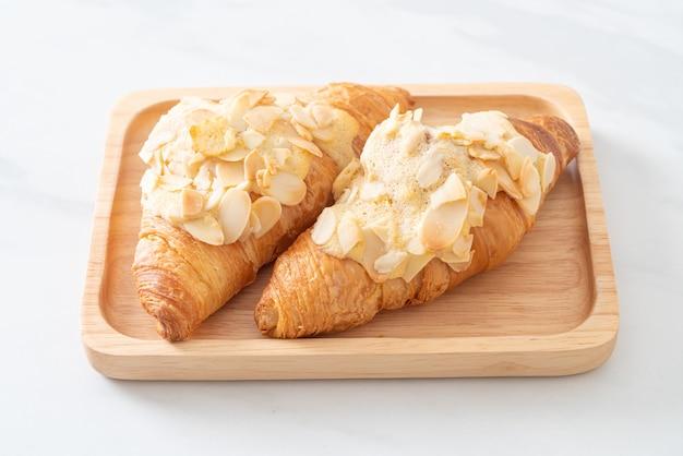 Croissant mit sahne und mandeln auf holzteller