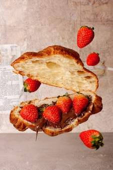 Croissant mit schokoladencreme und erdbeeren auf vintage-papierhintergrund fliegendes essen