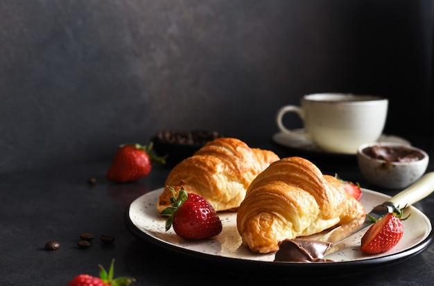 Croissant mit schokoladenpaste und einer tasse kaffee, erdbeeren auf dem küchentisch. â€traditioneller snack oder frã¼hstã¼ck.