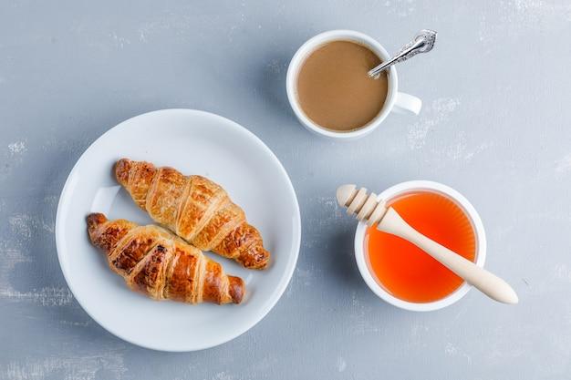 Croissant mit tasse kaffee, honig, schöpflöffel in einem teller, flach liegen.