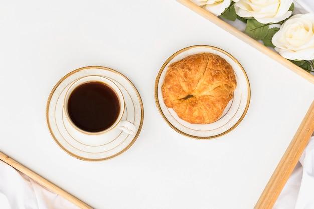 Croissant mit tasse tee auf hölzernen tablett
