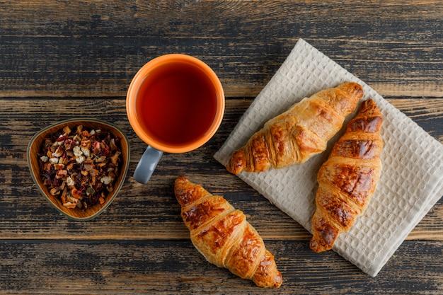 Croissant mit tee in einer tasse, getrocknete kräuter flach auf holz- und küchentuch gelegt