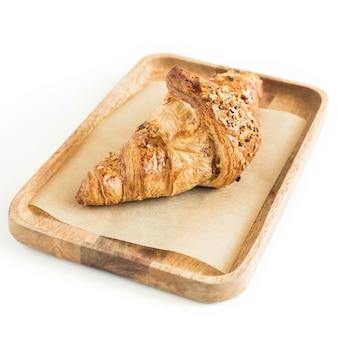 Croissant mit zerkleinerten nüssen auf einem holzserver isoliert