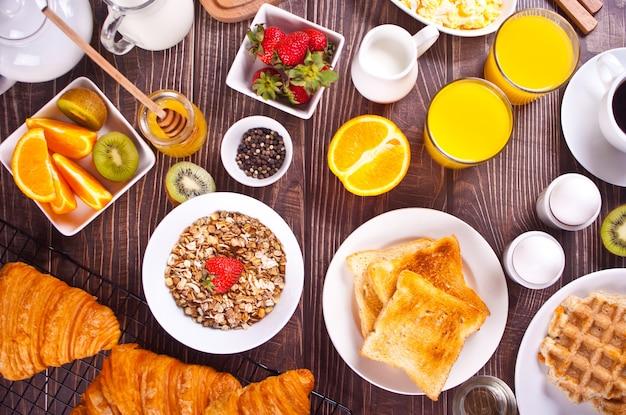 Croissant, müsli, toast, obst, eier, waffeln und eine tasse kaffee im hintergrund. frühstückskonzept