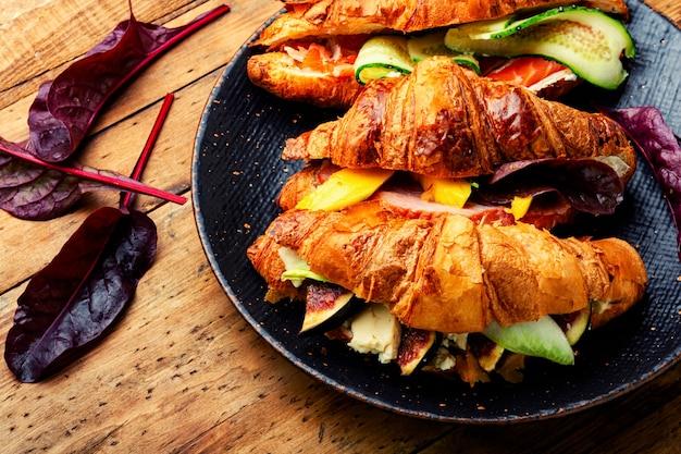 Croissant oder sandwich,morgenessen.croissants mit forelle, fleischspeck, gemüse und obst