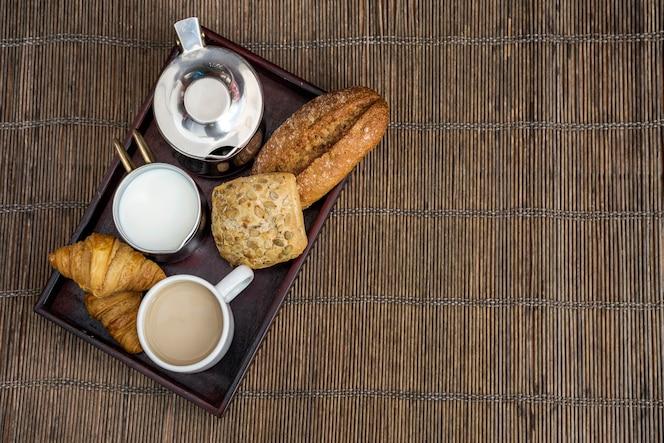 Croissant, plätzchen, brot mit tee und milch während des frühstücks