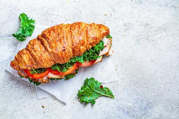 Croissant-sandwich mit fleisch, gemüse und grünkohl, weißer hintergrund. frühstückskonzept.