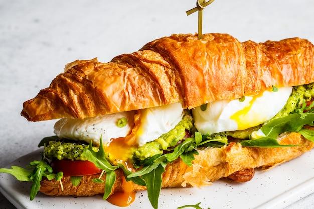 Croissant-sandwich mit pochiertem ei, tomate und guacamole auf weißem brett