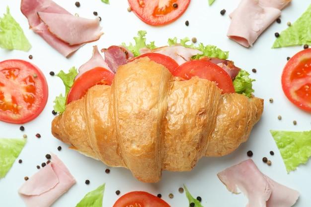 Croissant-sandwich und zutaten auf weiß, nahaufnahme