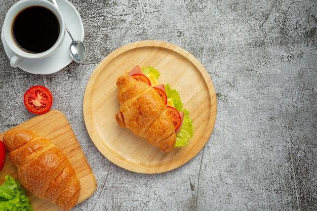Croissant-sandwiches auf dunkler holzoberfläche