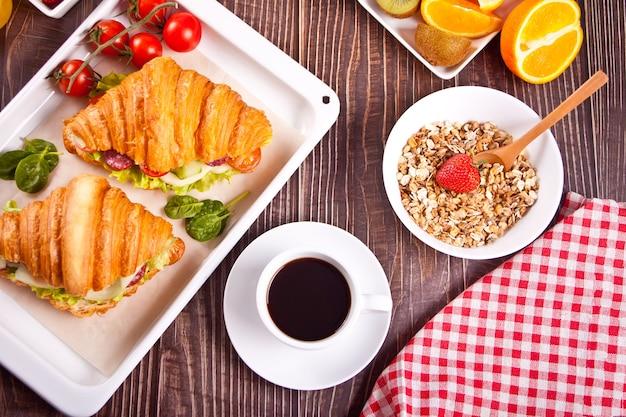 Croissant-sandwiches mit schinken, käse und gemüse. müsli, obst und eine tasse kaffee