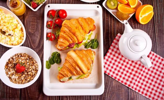 Croissant-sandwiches mit schinken, käsegrün, mit waffeln, orangensaft und früchten