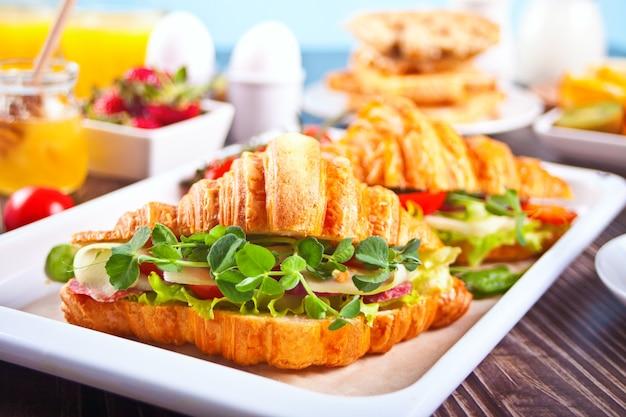 Croissant-sandwiches mit schinken, käsegrün