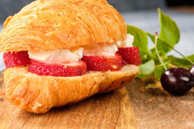 Croissant süßes sandwich mit frischkäse und erdbeeren auf einem holzbrett. nützliches frühstück. richtige ernährung. französische traditionelle gerichte.