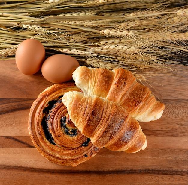 Croissant und brot denis der gerstenhintergrund auf holz