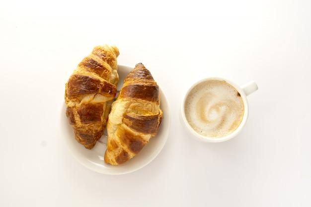 Croissant und eine tasse kaffee. frühstückskonzept. weißer hintergrund.