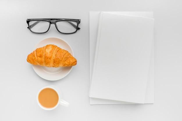 Croissant und eine tasse kaffee neben dem buch auf dem schreibtisch