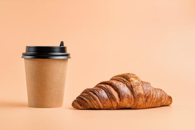 Croissant und einweggetränkeglas auf cremefarbenem hintergrund. kaffee und croissant.