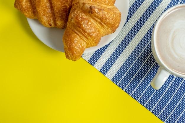 Croissant und heißer kakao oder heiße schokolade auf gelb