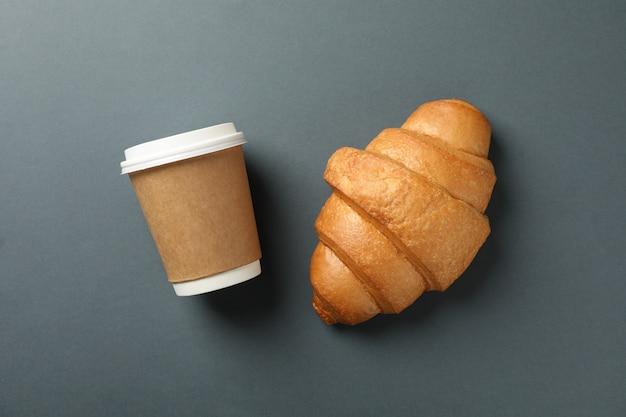 Croissant und pappbecher kaffee auf dunklem hintergrund, platz für text