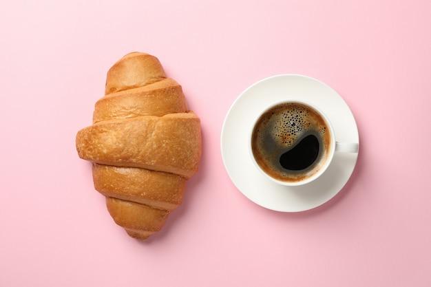 Croissant und tasse kaffee auf rosa hintergrund, draufsicht