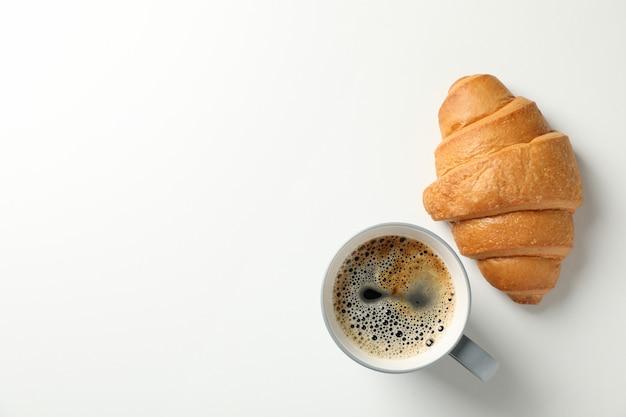 Croissant und tasse kaffee auf weißem hintergrund, draufsicht