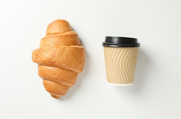 Croissant und tasse kaffee auf weißem hintergrund, platz für text