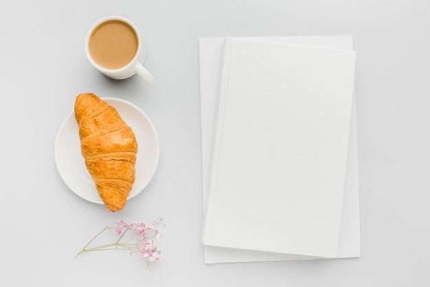 Croissant und tasse kaffee neben buch auf tisch